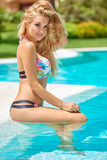 Adorable blond girl sitting in swimming pool Royalty Free Stock Photo