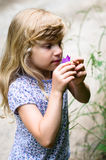 Adorable blond girl smelling pink flower Stock Photos