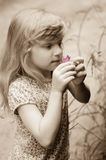 Adorable blond girl smelling pink flower Stock Image