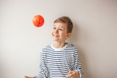 Adorable blond hair boy throwing basketball in the air. Kid standing against the wall and playing with basketball Stock Photo