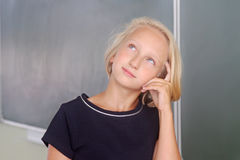 Adorable blond kid girl thoughtful in a classroom near a chalkboard. The child remembers, looking up thoughtfully. Back to school. Stock Photo