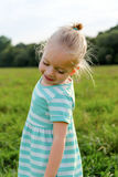 Adorable blond little girl with cheeky smile stock photos
