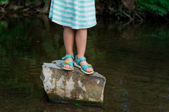 Adorable blond preschool girl playing in river stock photo