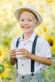 Adorable blond toddler boy funny eating bagel and drinking milk on summer sunflower field outdoors Stock Image