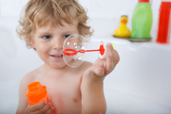 Adorable blond toddler boy playing with soap bubbles in bathtub Stock Photography