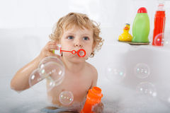 Adorable blond toddler boy playing with soap bubbles in bathtub Stock Images
