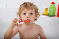 Adorable blond toddler boy playing with soap bubbles in bathtub Stock Image