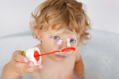 Adorable blond toddler boy playing with soap bubbles in bathtub Royalty Free Stock Photos