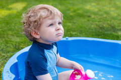 Adorable blond toddler boy playing with water, outdoors. Royalty Free Stock Images