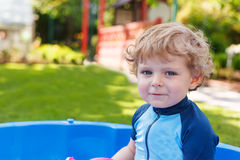Adorable blond toddler boy playing with water, outdoors. Royalty Free Stock Photo