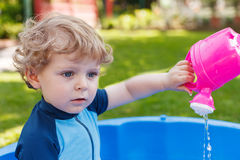 Adorable blond toddler boy playing with water, outdoors. Royalty Free Stock Image