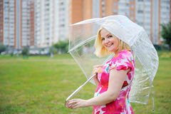 Adorable blond woman poses outdoors with umbrella Stock Image