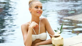Adorable blond woman standing in swimming pool Stock Photo