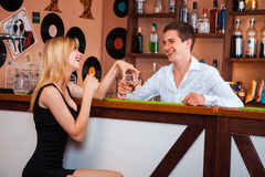 Adorable blonde in a black dress flirting with barman Royalty Free Stock Photo