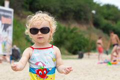 Adorable blonde curly hair little girl in fashionable sunglasses Royalty Free Stock Image
