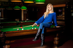 Adorable blonde fashion woman posing on pool table with the cue Royalty Free Stock Photography
