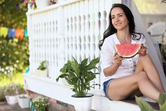 Adorable blonde girl eats a slice of watermelon outdoor Stock Photo