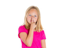 Adorable blonde girl putting finger up to lips and saying shhh Stock Photos