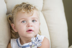Adorable Blonde Haired and Blue Eyed Little Girl in Chair Royalty Free Stock Photography