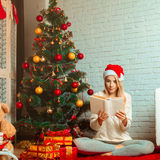 Adorable blonde reads fairy tale on Christmas Eve in santa hat Royalty Free Stock Photography