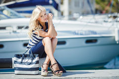 Adorable blonde sits against a backdrop of yachts Stock Photos