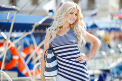 Adorable blonde sits against a backdrop of yachts Royalty Free Stock Images