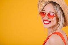 Adorable blonde woman with big teeth smile in straw hat on bright yellow background. Heart shaped pink sunglasses. Summer time royalty free stock image