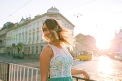 Adorable blonde woman with charming smile posing at the sunrise. Adorable  blonde young woman with charming smile posing at the sunrise and sun glare Royalty Free Stock Image