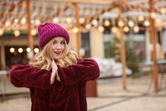 Adorable young woman wearing red knitted hat and winter coat, po Stock Photography
