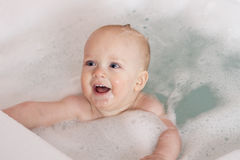 Adorable blue-eyed baby boy playing in a bathtub. Cute infant kid swimming in a tub Royalty Free Stock Photography