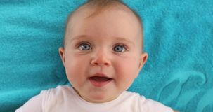 Cute baby lying on towel. Adorable blue eyed baby with opened mouth lying on blue towel and looking at camera stock video footage