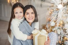 Adorable blue eyed small kid huggs with great love her mother who holds wrapped gift box, stand near decorated New Year tree, happ stock photography