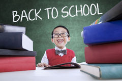 Adorable boy back to school and smiling in class Royalty Free Stock Images