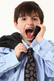 Adorable Boy in Baggy Suit with Cellphone. Adorable seven year old french american boy in over sized suit over white background yelling in cellphone Royalty Free Stock Image