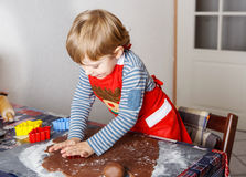 Adorable boy baking ginger bread cookies for Christmas Stock Photo