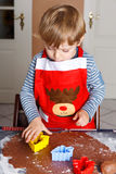Adorable boy baking ginger bread cookies for Christmas Royalty Free Stock Photos