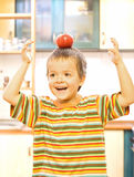 Adorable boy balancing a red apple Stock Image