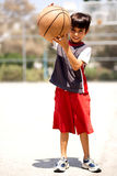 Adorable boy with basketball. Outdoors Stock Images