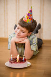 Adorable boy with birthday cake on the floor Royalty Free Stock Images