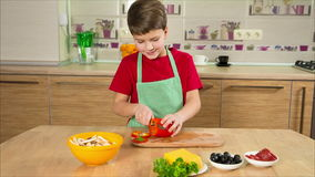 Adorable boy cutting the paprika in kitchen stock footage