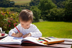 Adorable boy, drawing a painting in a book, outdoor Stock Photo