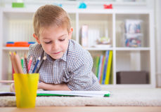 Adorable boy draws at home Stock Images