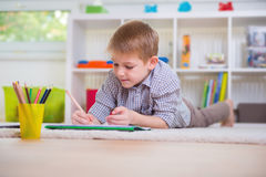 Adorable boy draws at home Stock Photography