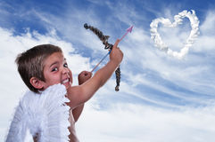 Adorable boy dressed as Cupid. On blue sky Royalty Free Stock Photo