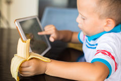 Adorable boy, eating his banana, while watching movie on tablet Stock Photos