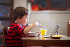 Adorable boy, eating his supper, while watching movie Royalty Free Stock Photography