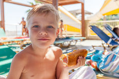 Adorable boy eating hot dog at the beach aquapark. Adorable kid boy eating hot dog at the beach aquapark Royalty Free Stock Photos