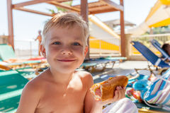 Adorable boy eating hot dog at the beach aquapark Royalty Free Stock Photos