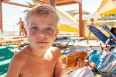 Adorable boy eating hot dog at the beach aquapark. Adorable kid boy eating hot dog at the beach aquapark Royalty Free Stock Images