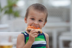 Adorable boy, eating pizza royalty free stock image